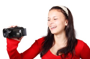 Girl recording with a video camera.