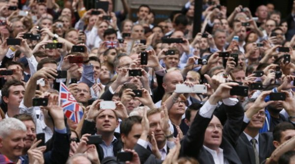 Spectators take pictures with their smartphones as they watch a parade celebrating Britain's athletes who competed in the London 2012 Olympic and Paralympic Games in central London on September 10, 2012. Britain was bidding a fond farewell om September 10 to a golden summer of Olympic and Paralympic sport with a victory parade by athletes through London ending up at Buckingham Palace. AFP PHOTO / POOL / STEFAN WERMUTH        (Photo credit should read STEFAN WERMUTH/AFP/GettyImages)